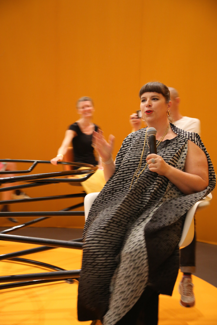Joana Vasconcelos legt het concept uit van 'Meeting point'. Een grote-mensen-draaimolen gemaakt van oude stoelen uit directiekamers.